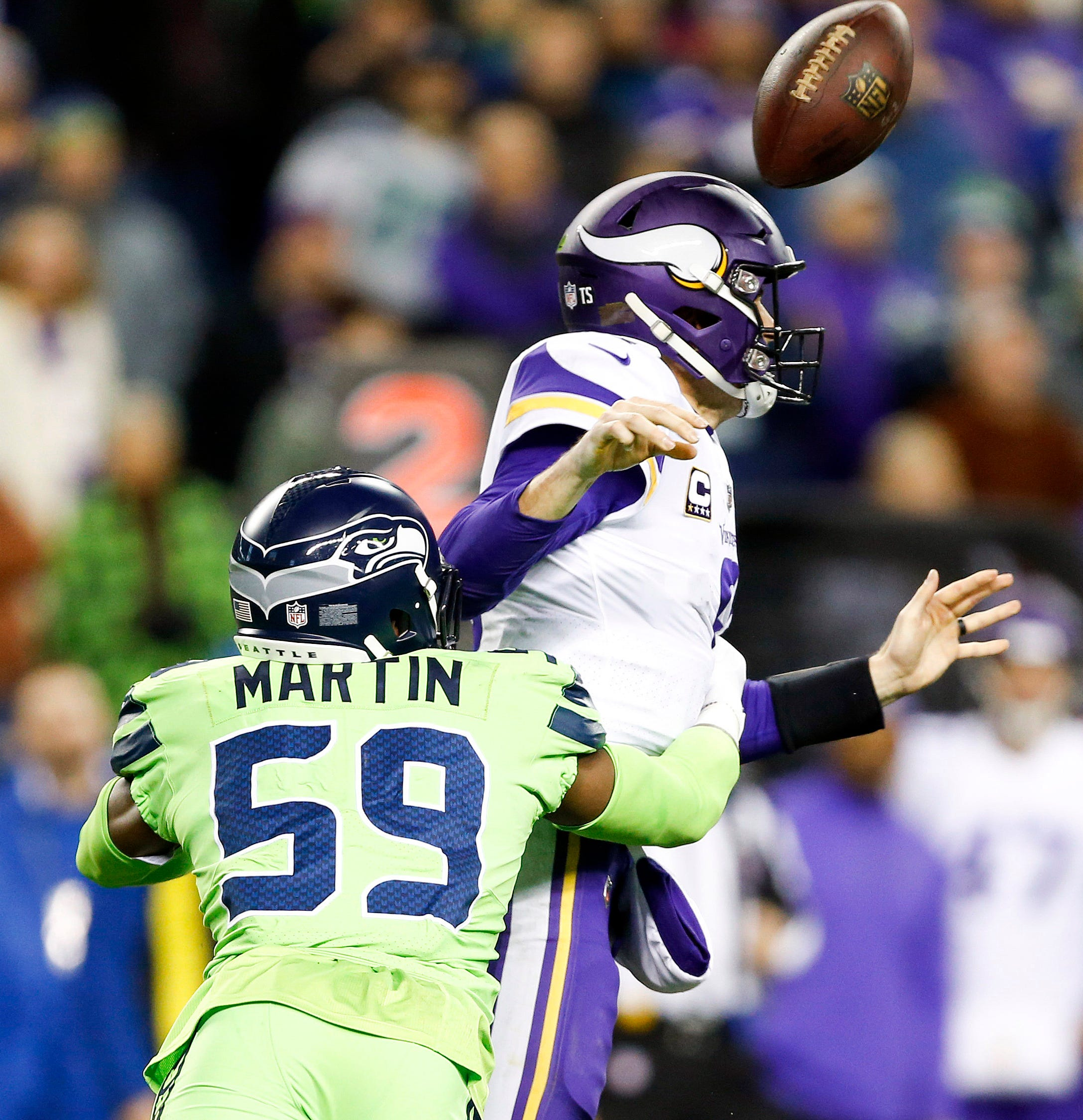 Seattle Seahawks linebacker Jake Martin forces a fumble by Minnesota Vikings quarterback Kirk Cousins during the fourth quarter at CenturyLink Field. The fumble was returned for a touchdown.