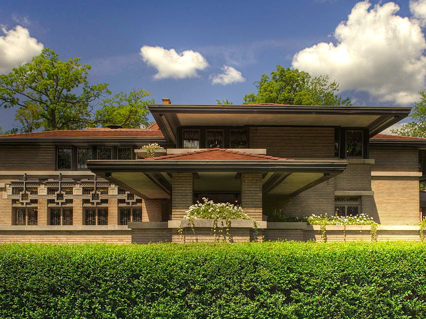 "Meyer May House, Grand Rapids, 1908 (Architect: Frank Lloyd Wright): Located on the southern edge of the Heritage Hill Historic District in Grand Rapids, the Meyer May House is an ideal example of Frank Lloyd Wright's Prairie Style of architecture. The beautiful horizontality is emphasized by shallow-hipped roofs, broad overhangs, raked horizontal brick joints and limestone trim details. The home includes many of Wright's trademark details, including copper ornament, stone urns, garden planter walls and leaded art glass. It was the first Frank Lloyd Wright project in Michigan and has been called ""Michigan's Prairie Masterpiece."" The house was purchased and meticulously restored to its original condition by Steelcase in 1987 and is the most completely restored of Frank Lloyd Wright-designed homes. The house is owned by Steelcase and is open for tours."