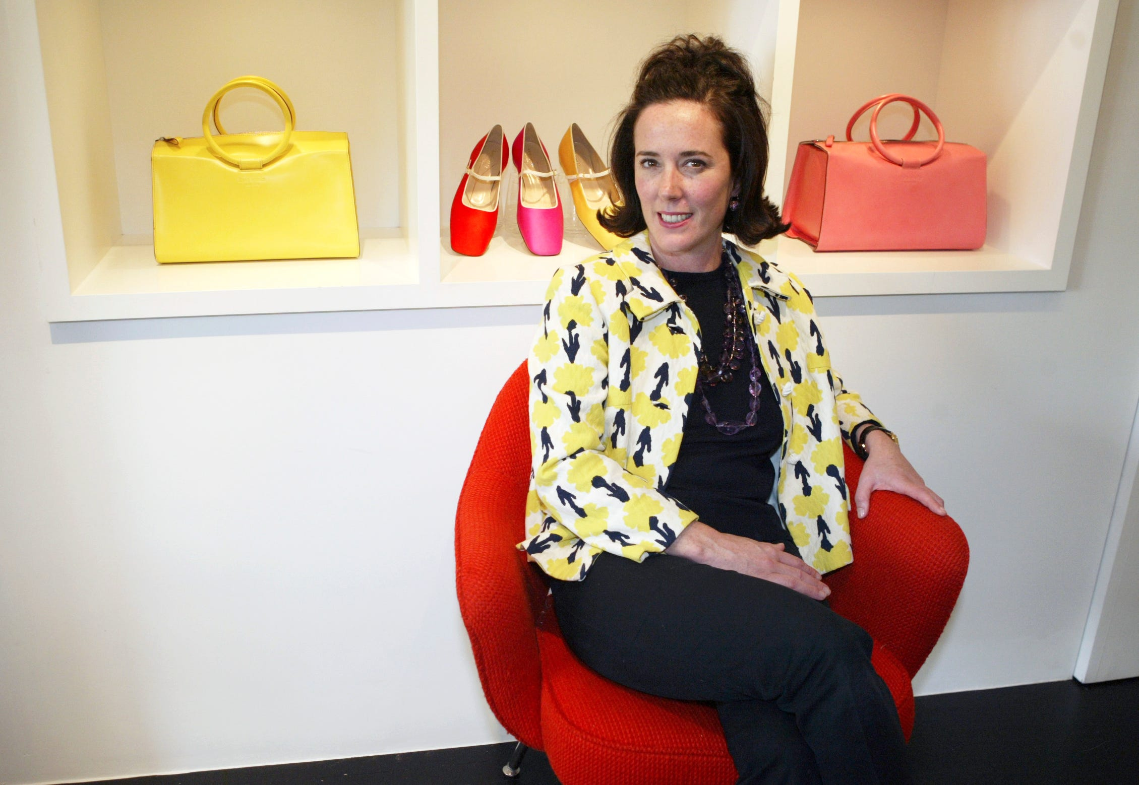 Designer Kate Spade poses among handbags and shoes from her collection in New York on May 13, 2004.