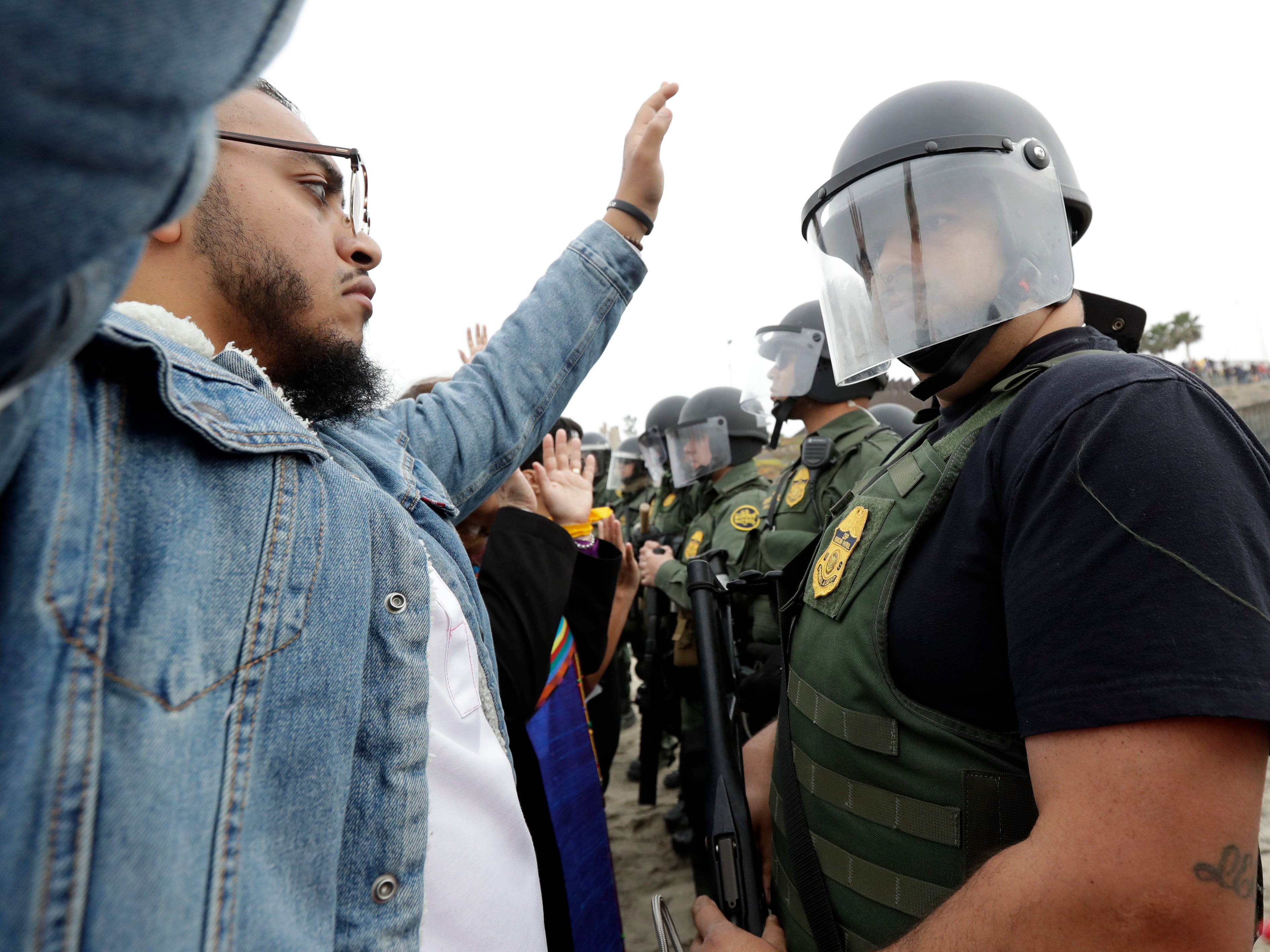 A man holds his hands in the air in front of a line of U.S. Border Patrol agents during a protest on Dec. 10, 2018, in San Diego.