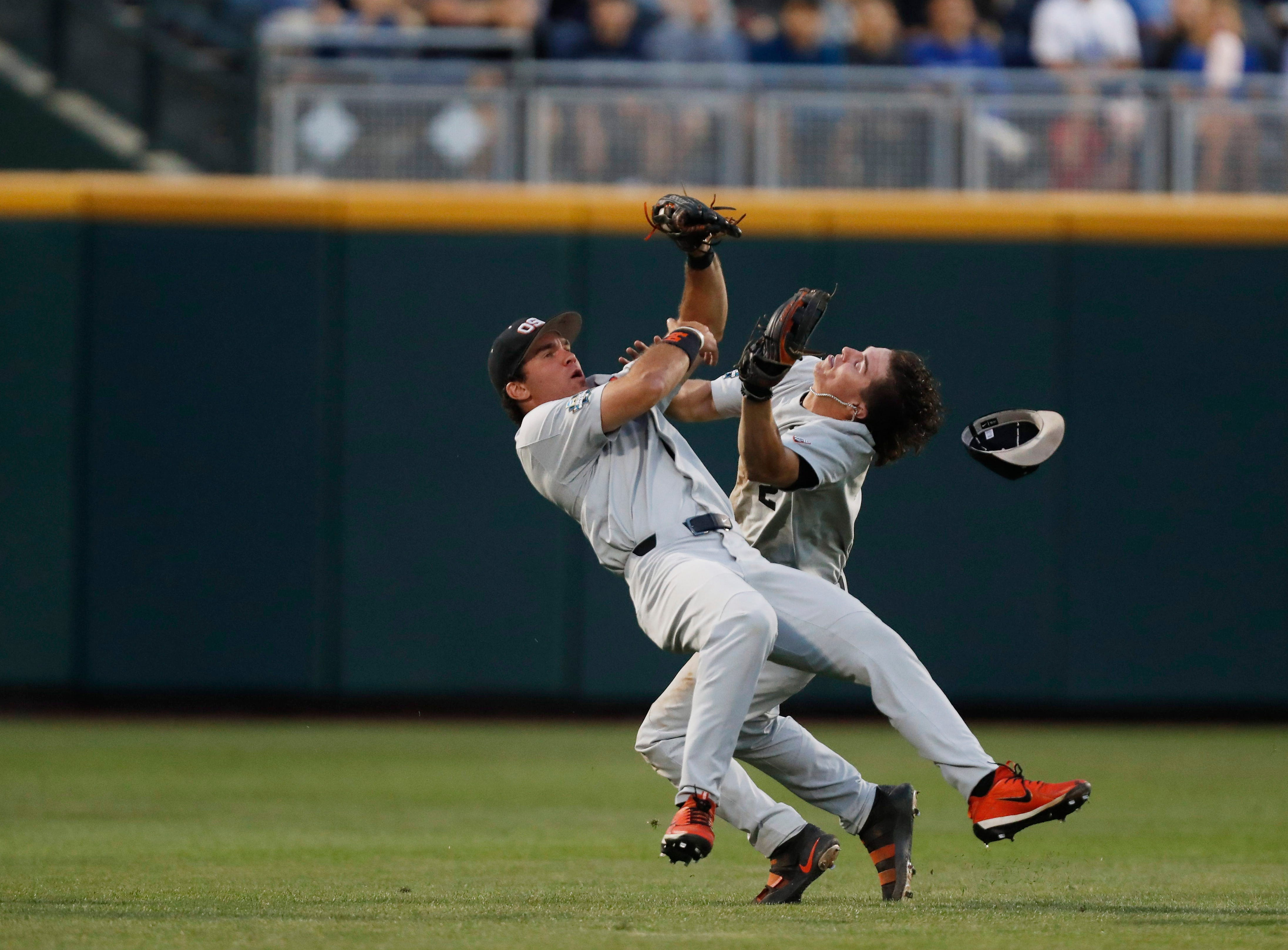 June 20: Oregon State Beavers center fielder Jack Anderson makes a catch while colliding with shortstop Cadyn Grenier (2) during the fourth inning of a College World Series game against the North Carolina Tar Heels.
