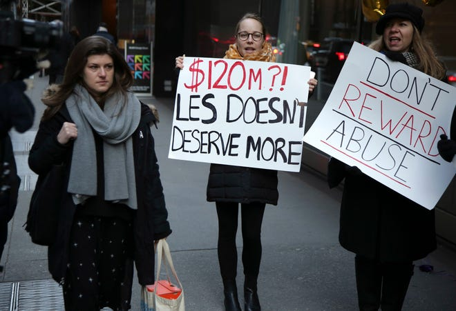Protesters tote signs outside the CBS shareholder's meeting in New York, which wrapped up quickly on Dec. 11, 2018, without discussing scandal-plagued ex-CEO Les Moonves will get his $120 million severance package.