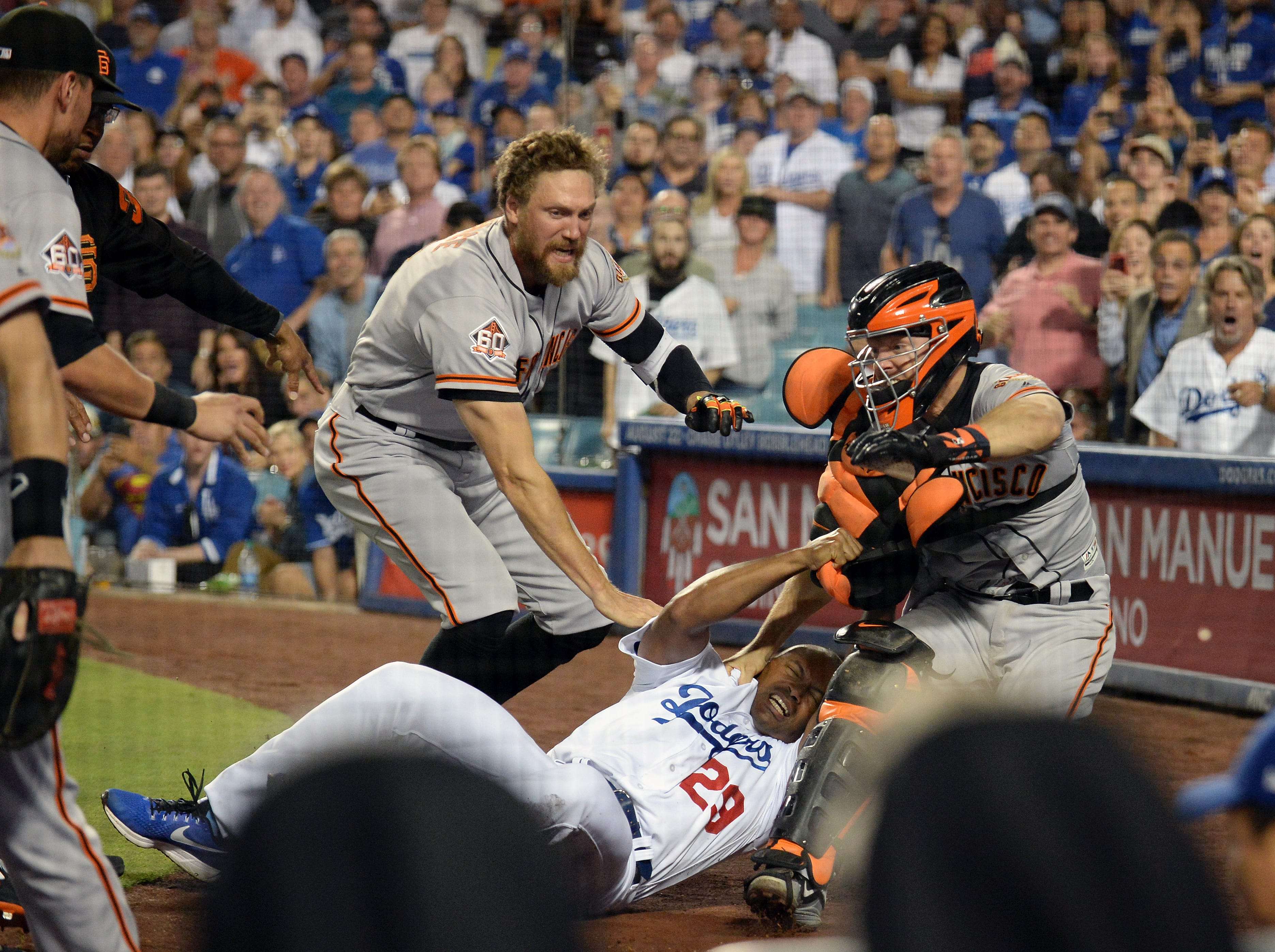 Aug. 14: Los Angeles Dodgers first base coach George Lombard (29) is brought down by San Francisco Giants catcher Nick Hundley (5) and right fielder Hunter Pence (8) during a seventh-inning brawl at Dodger Stadium.