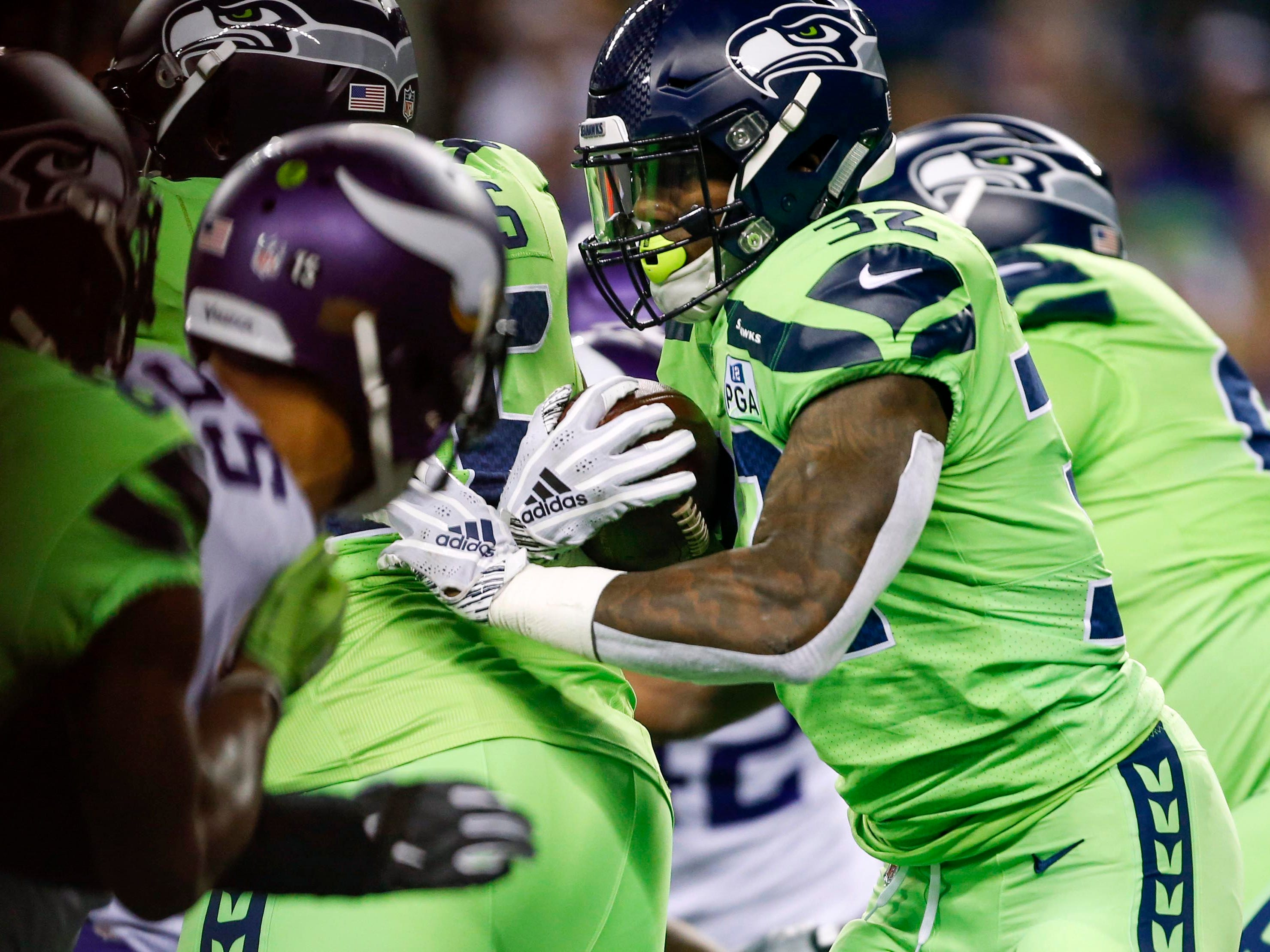 Seattle Seahawks running back Chris Carson (32) rushes against the Minnesota Vikings during the first quarter at CenturyLink Field.