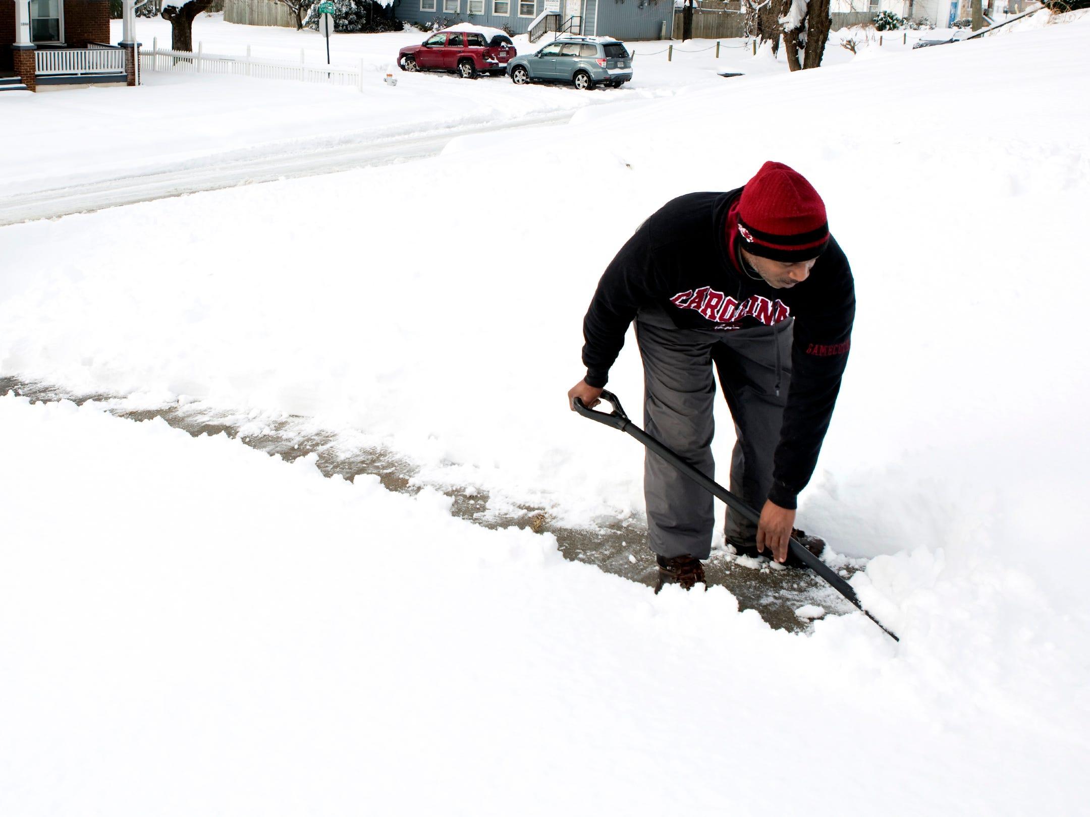 Jamie Price shovels snow for a friend on Dec. 10, 2018, in Roanoke, Va.