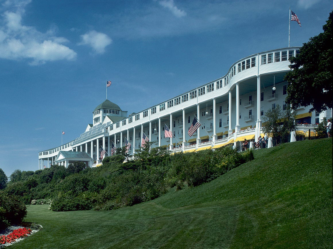 Grand Hotel, Mackinac Island, 1887 (Architect: George Mason of Mason and Rice; historic preservation architect: HopkinsBurns Studio): This breathtakingly beautiful hotel is one of the best surviving examples of wood Victorian beach resorts in America. The expansive Colonial Revival hotel is located on Mackinac Island in the sparkling waters of Lake Huron. Built of Michigan white pine, the structure was completed in a mere 93 days. The hotel is five stories high, crowned by a central cupola, and its unmissable three-story porch is the largest in the world at 660 feet. Wonderfully slender columns support the porch and frame the views of Lake Huron and the Mackinac Bridge, an engineering marvel and longest suspension bridge in the Western Hemisphere. Grand Hotel is an architectural icon of Mackinac Island and Michigan.
