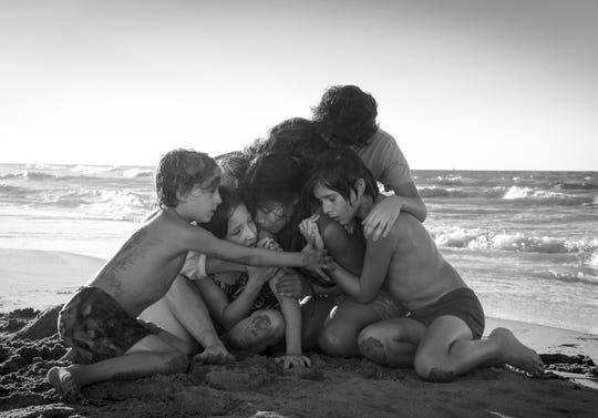 """This image released by Netflix shows Yalitza Aparicio, center, in a scene from the film """"Roma,"""" by filmmaker Alfonso Cuaron. On Thursday, Dec. 6, 2018, the film was nominated for a Golden Globe award for best foreign language film. The 76th Golden Globe Awards will be held on Sunday, Jan. 6. (Carlos Somonte/Netflix via AP) ORG XMIT: NYET859"""
