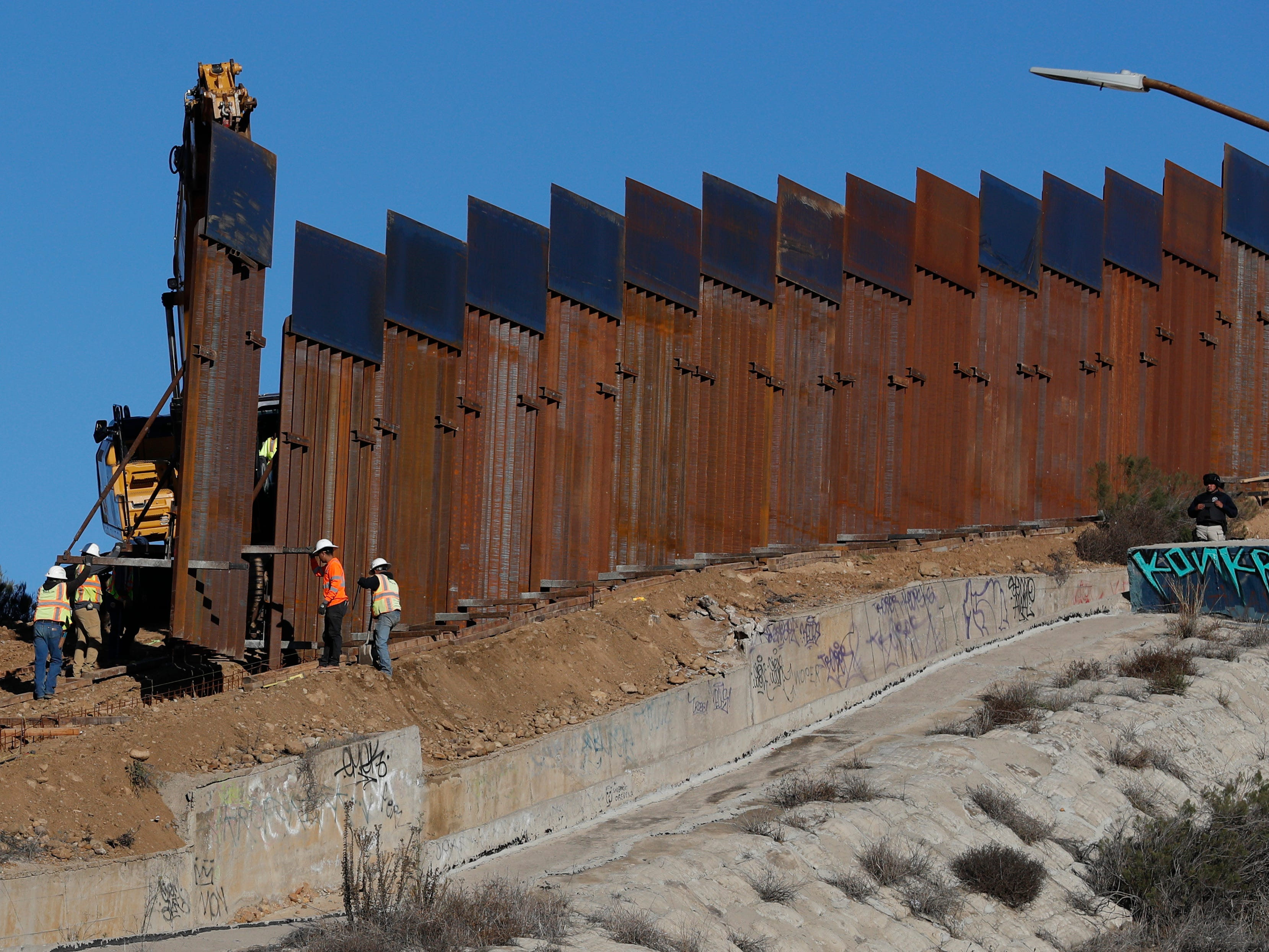 Workers add new sections to the border wall in Tijuana, Mexico on Dec. 8, 2018.
