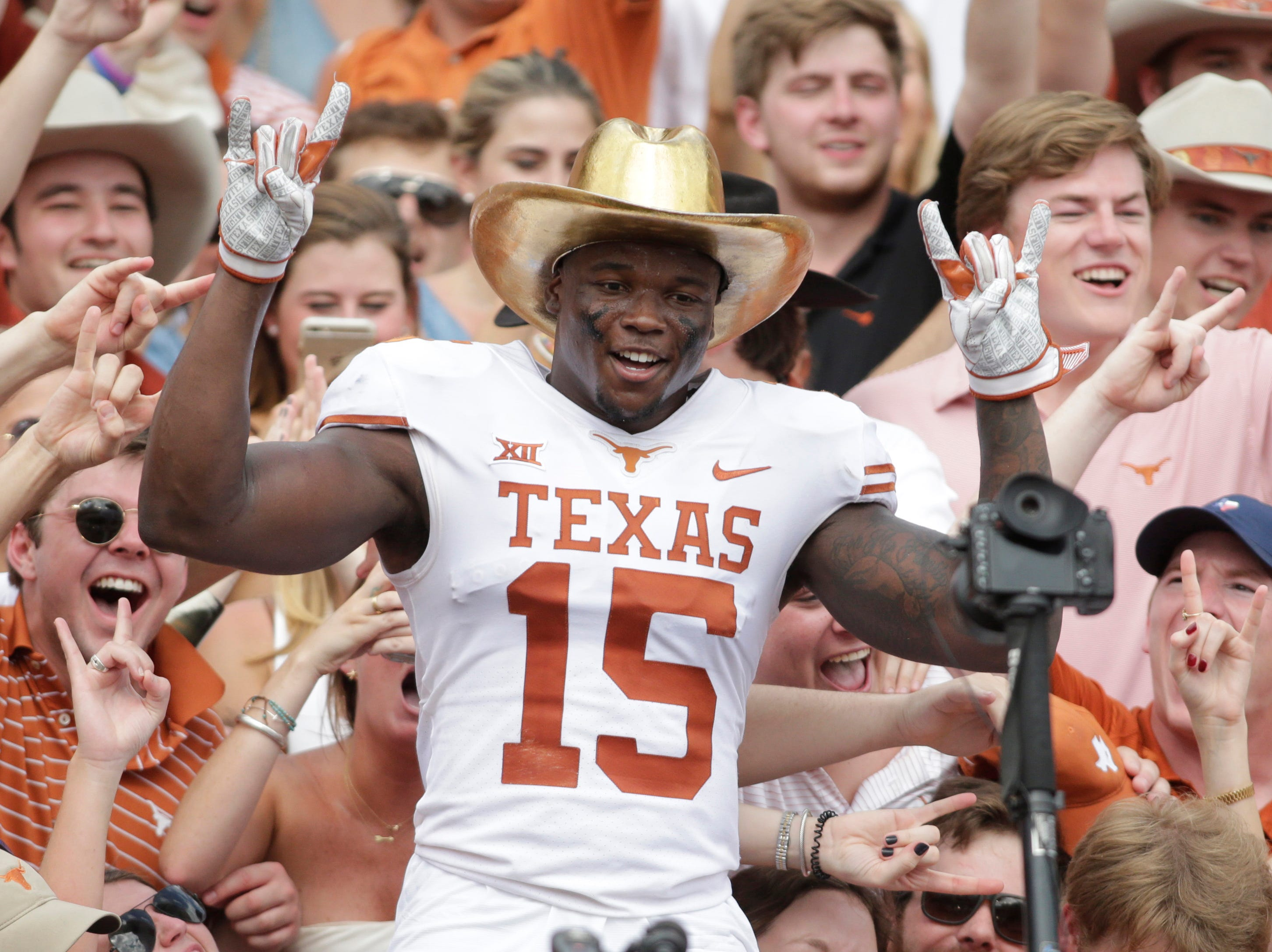 Oct. 6: Texas Longhorns defensive back Chris Brown celebrates in the crowd with the Golden Hat after beating the Oklahoma Sooners at the Cotton Bowl.