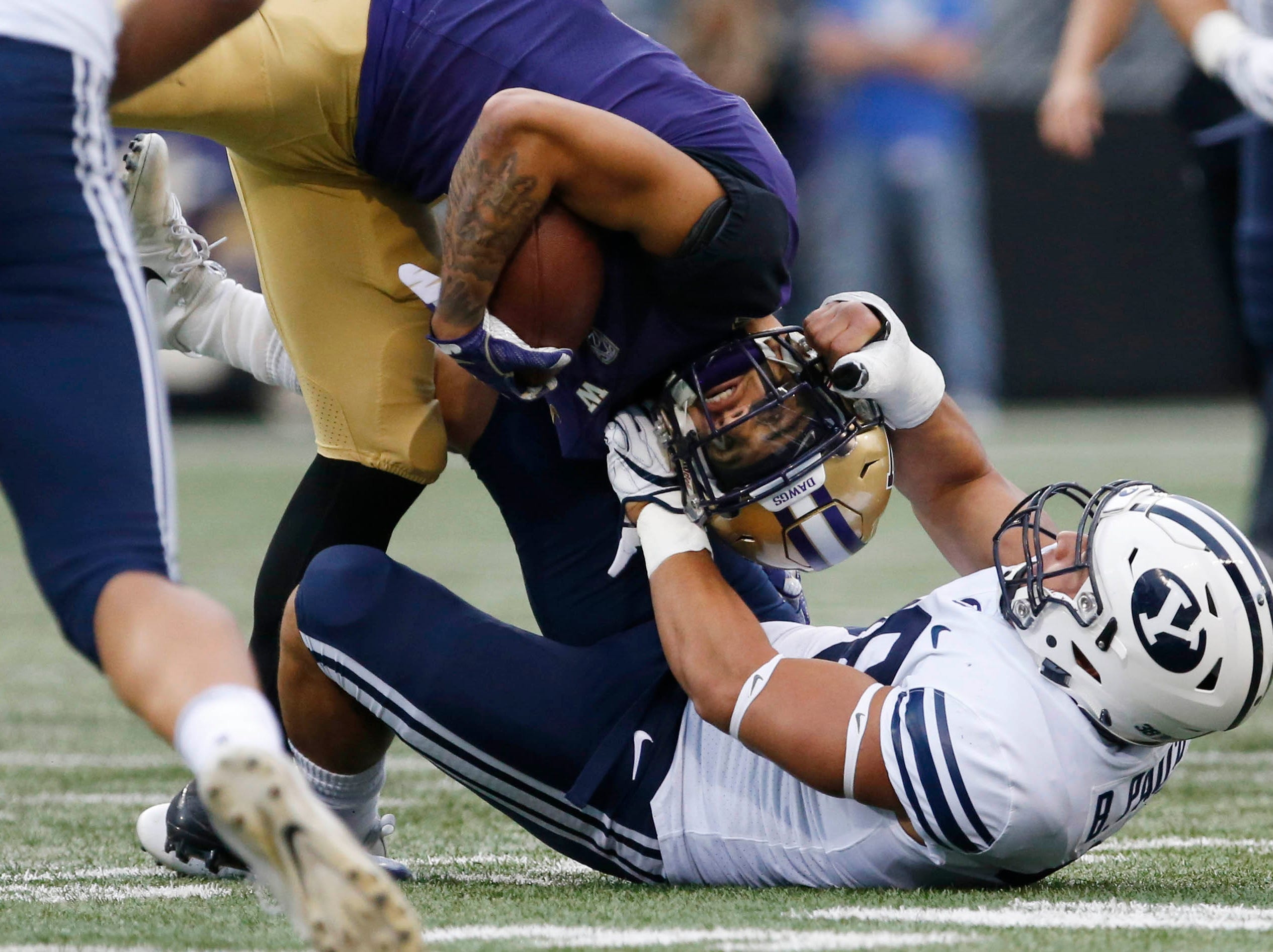 Sept. 29: Washington Huskies wide receiver Aaron Fuller (2) is pulled down by his helmet by Brigham Young Cougars linebacker Butch Pau'u (38) during the first quarter at Husky Stadium.