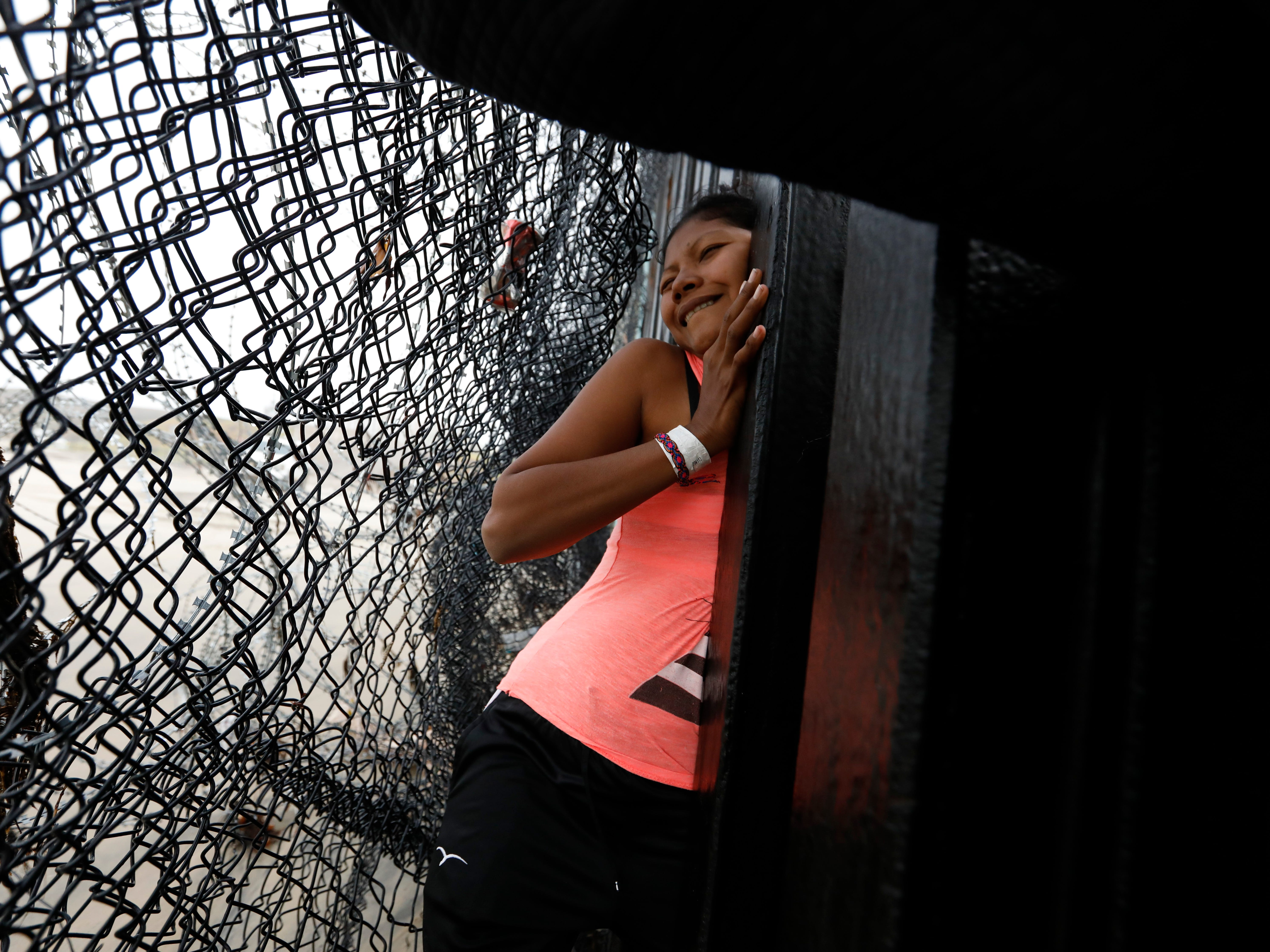 A Honduran migrant, followed by her daughter, squeezes through a gap in the border wall near Tijuana, Mexico on Dec. 9, 2018. Discouraged by the long wait to apply for asylum through official ports of entry, many Central American migrants from recent caravans are choosing to cross the U.S. border wall illegally and hand themselves in to Border Patrol agents to request asylum.