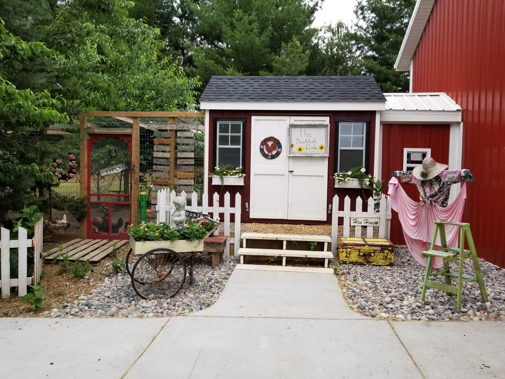 "The entryway to Danielle Raad's ""The Breakfast Club"" hen house features barn-red siding, a white picket fence, flower boxes and a scarecrow."
