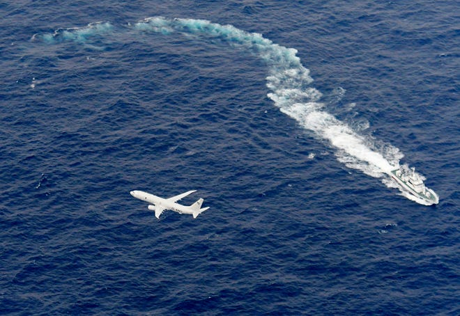 In this Dec. 6 aerial photo, Japan's Coast Guard ship, top, and U.S. military plane are seen at sea off Kochi, southwestern Japan, during the search and rescue operation for missing crew members of the U.S. Marine refueling plane and fighter jet.