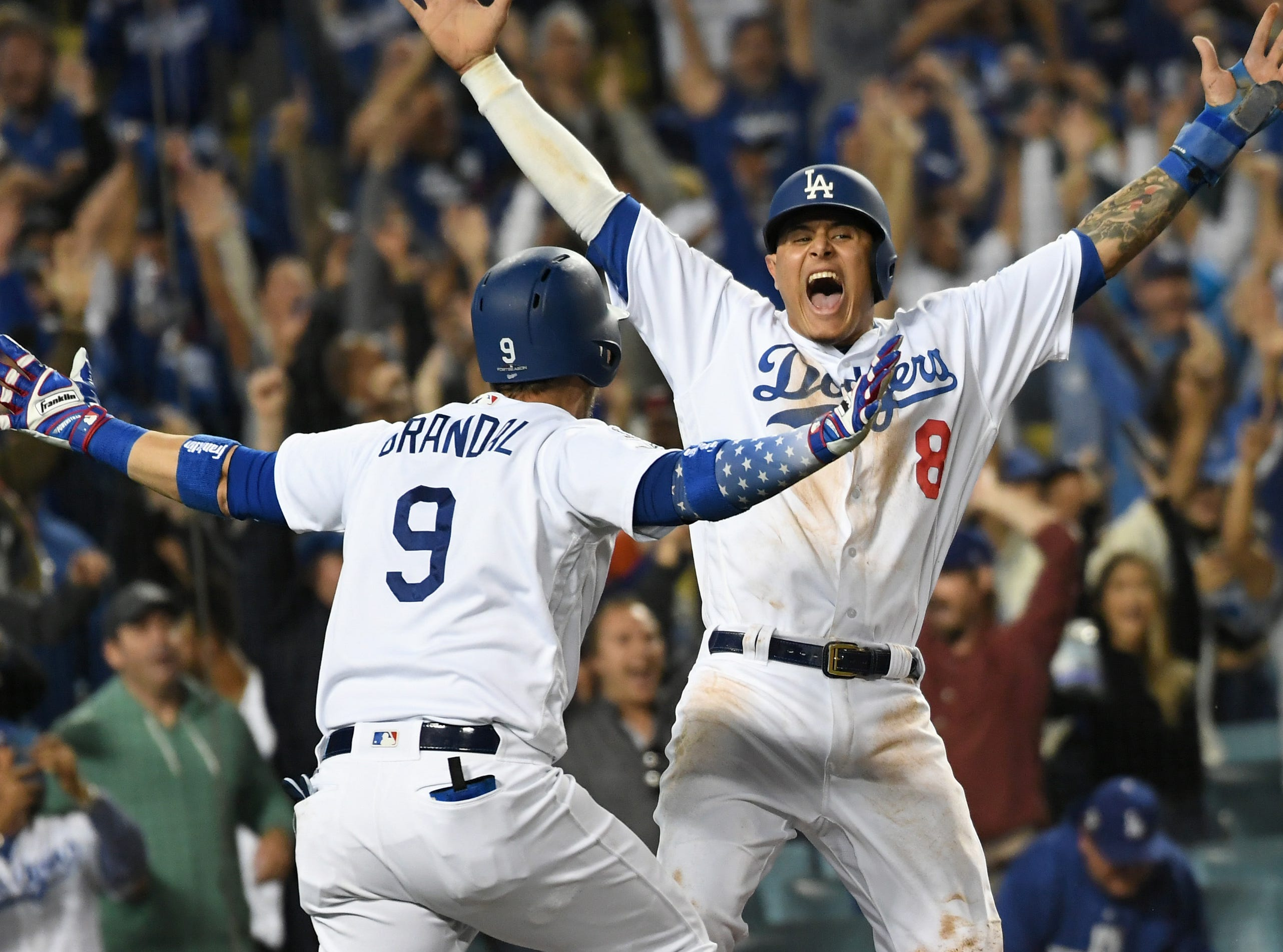 Oct. 16: Los Angeles Dodgers shortstop Manny Machado (8) celebrates with catcher Yasmani Grandal after scoring on an RBI single by center fielder Cody Bellinger in the 13th inning in Game 4 of the NLCS.