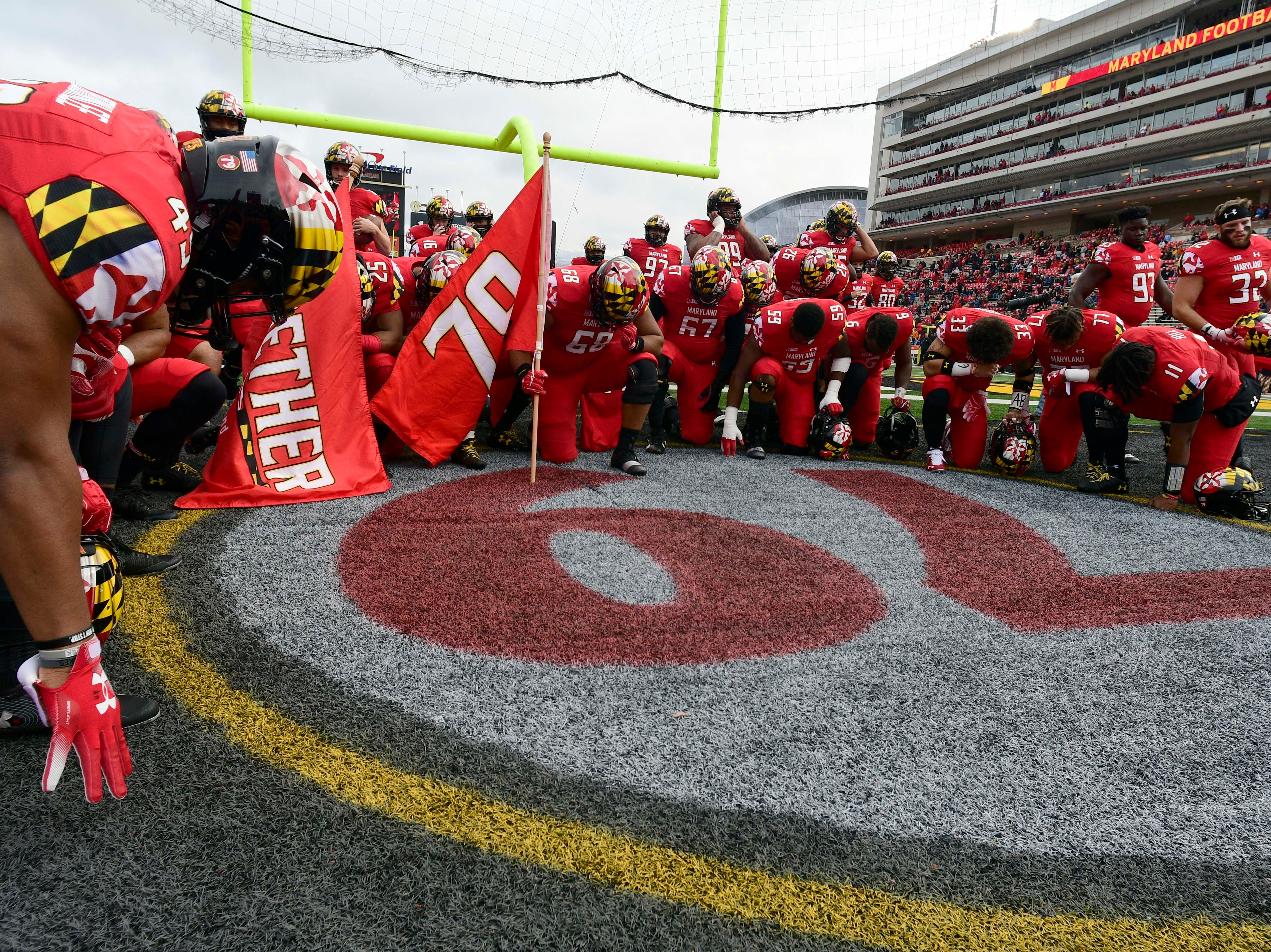 Oct. 27: Maryland Terrapins players take a knee in front of late teammate Jordan McNair's number before the game against the Illinois Fighting Illini at Capital One Field at Maryland Stadium.