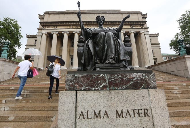 People walk past the Alma Mater statue on the Columbia University campus on July 1, 2013 in New York City.