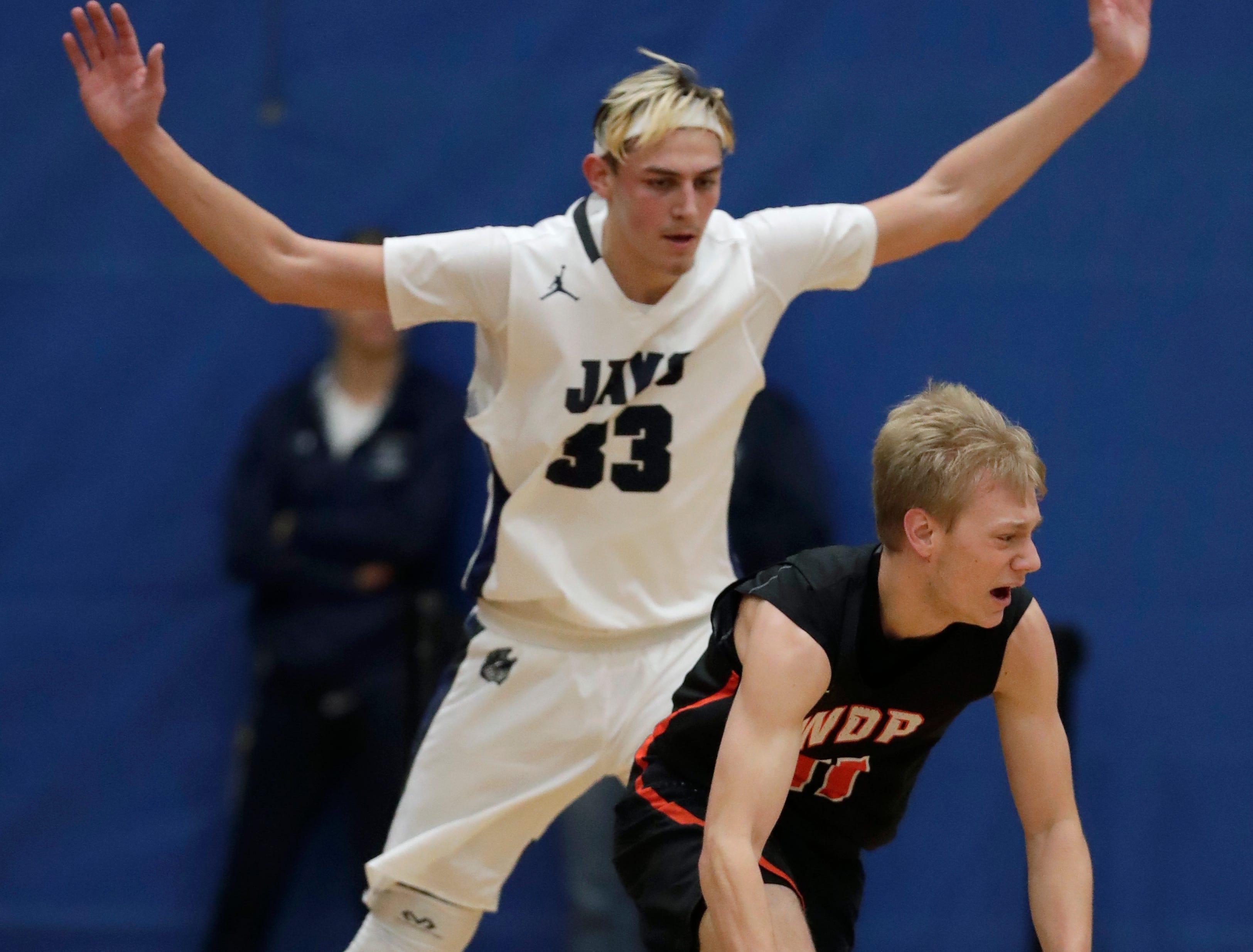 Menasha High School's Ben Romnek (33) defends against West De Pere High School's Brady Darrow (11) during their boys basketball game Tuesday, December 11, 2018, in Menasha, Wis. Dan Powers/USA TODAY NETWORK-Wisconsin
