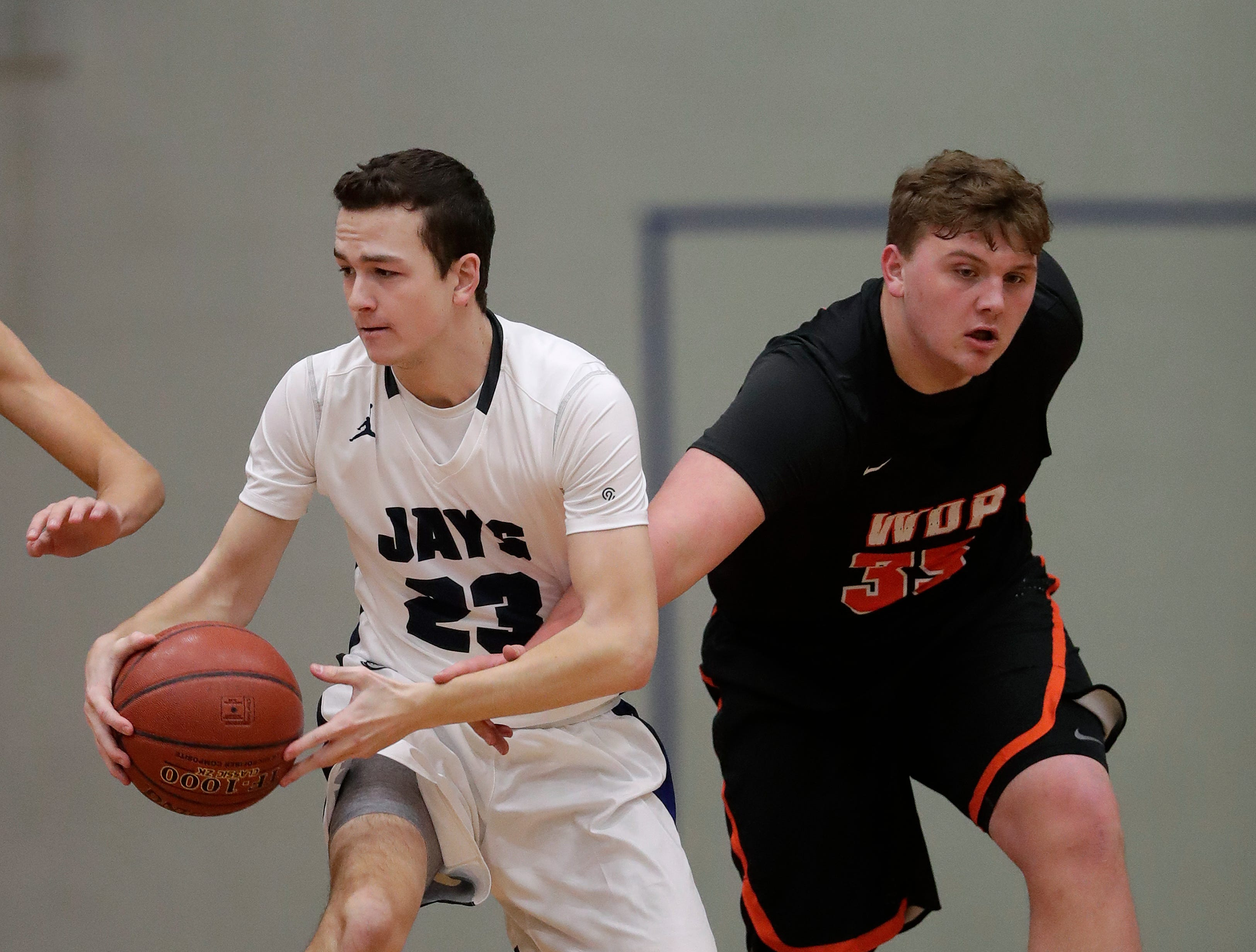 Menasha High School's Duncan Dotterweich (23) controls the ball against West De Pere High School's Kerry Kondanko (35) during their boys basketball game Tuesday, December 11, 2018, in Menasha, Wis. Dan Powers/USA TODAY NETWORK-Wisconsin