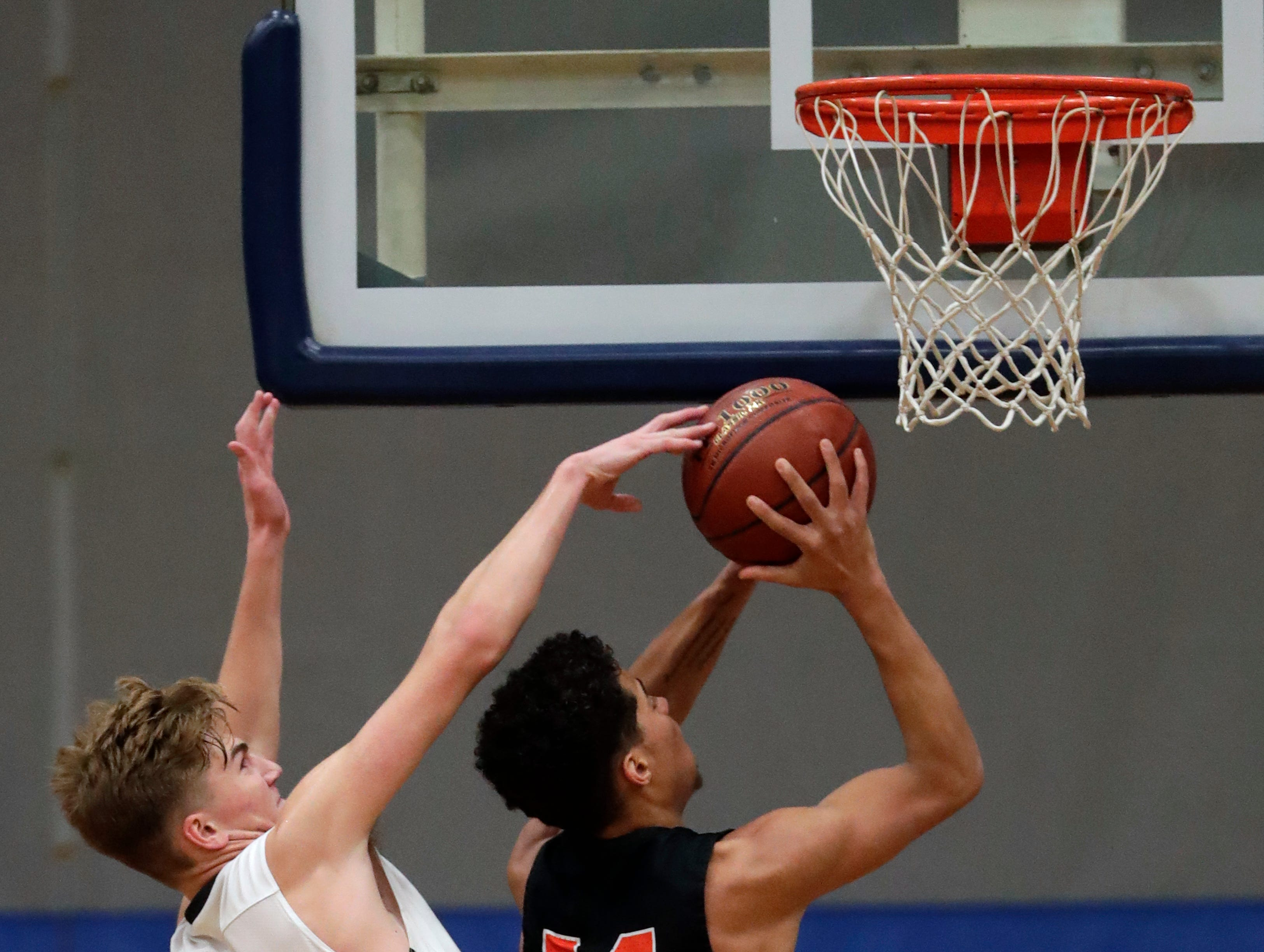 Menasha High School's Jacob Everson (4) tries to block a shot against West De Pere High School's Jovan Webb (14) during their boys basketball game Tuesday, December 11, 2018, in Menasha, Wis. Dan Powers/USA TODAY NETWORK-Wisconsin