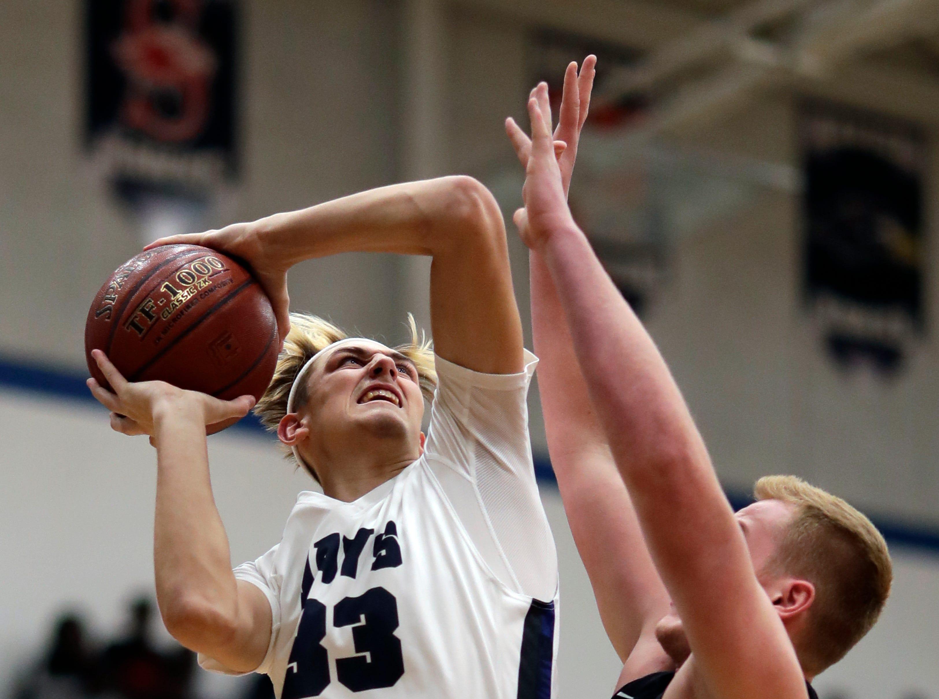 Menasha High School's Ben Romnek (33) puts up a shot against West De Pere High School's Jacob Karchinski (32) during their boys basketball game Tuesday, December 11, 2018, in Menasha, Wis. Dan Powers/USA TODAY NETWORK-Wisconsin