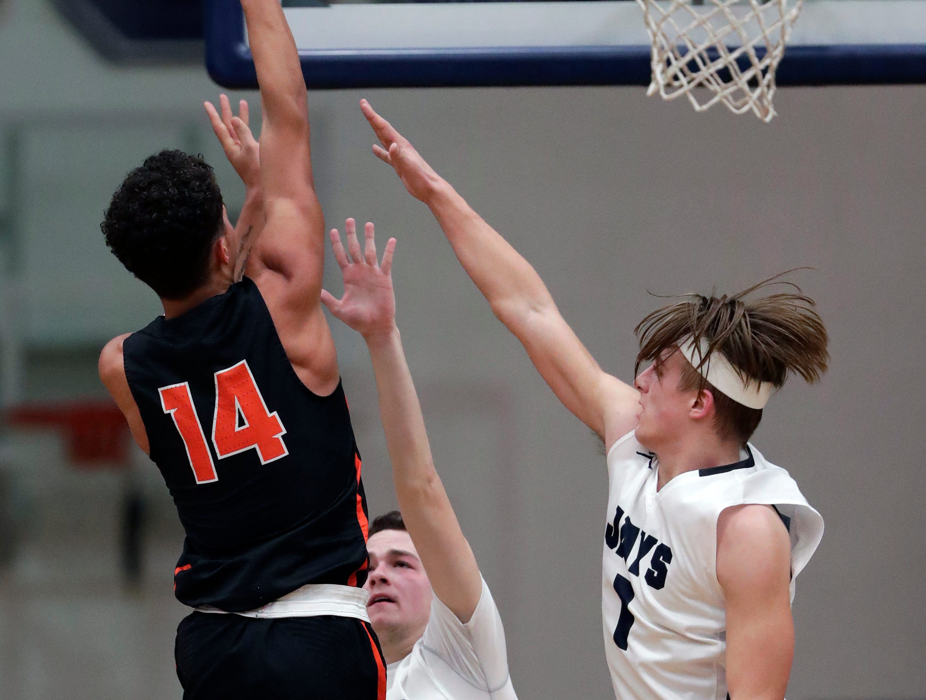 Menasha High School's Duncan Dotterweich (23) and Jay Pawlowski (1) defend against West De Pere High School's Jovan Webb (14) during their boys basketball game Tuesday, December 11, 2018, in Menasha, Wis. Dan Powers/USA TODAY NETWORK-Wisconsin