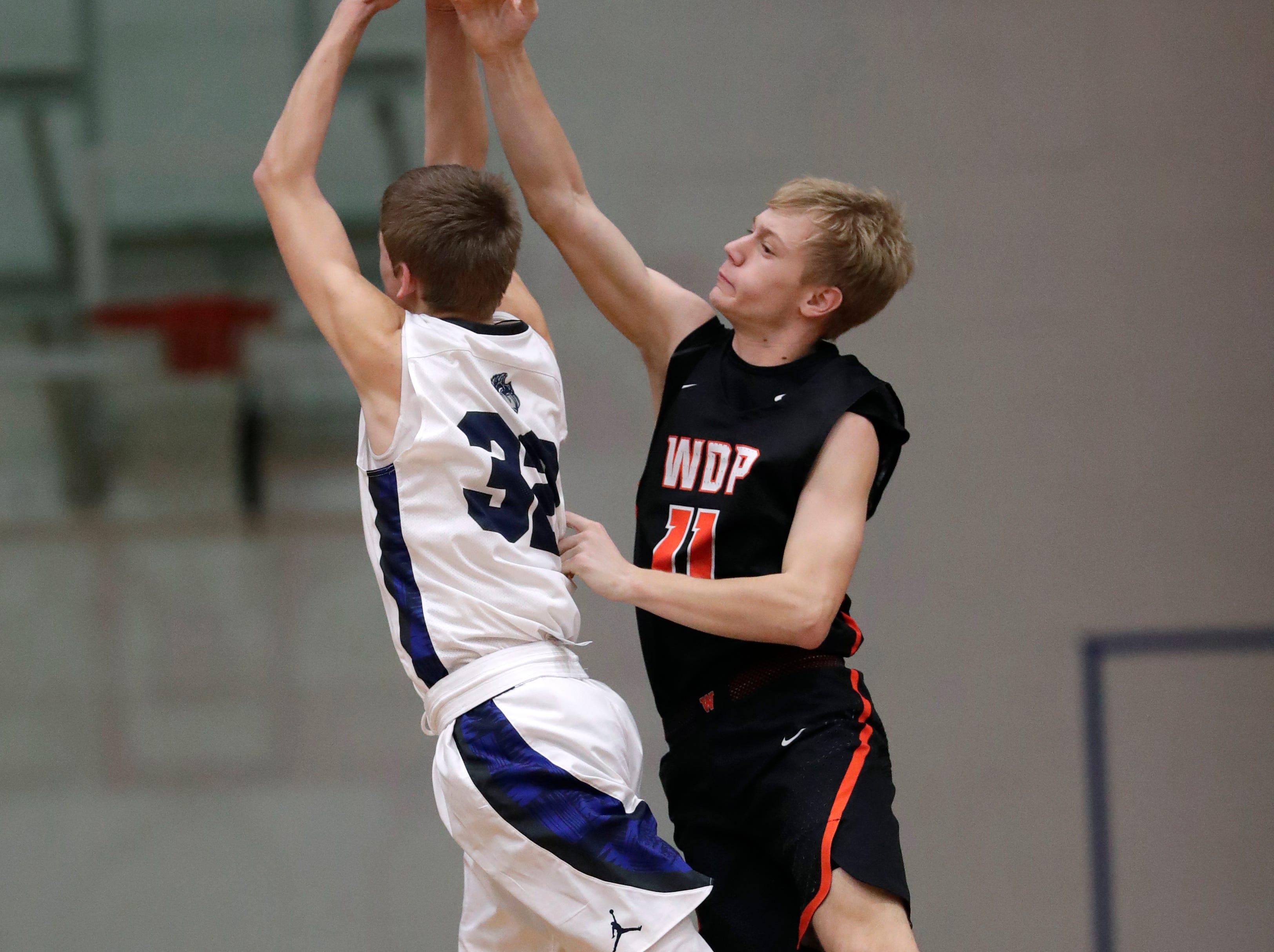 Menasha High School's Jordan Nowak (32) puts up a shot against West De Pere High School's Brady Darrow (11) during their boys basketball game Tuesday, December 11, 2018, in Menasha, Wis. Dan Powers/USA TODAY NETWORK-Wisconsin