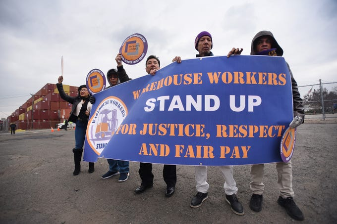 Workers including, Eugenio Aracena (R) who works at the warehouse of HM hold a banner prior to a press conference at the Port of Newark to call for greater protections for warehouse workers, photographed at the corner of Corbin and Marsh streets in Newark on 12/12/18.