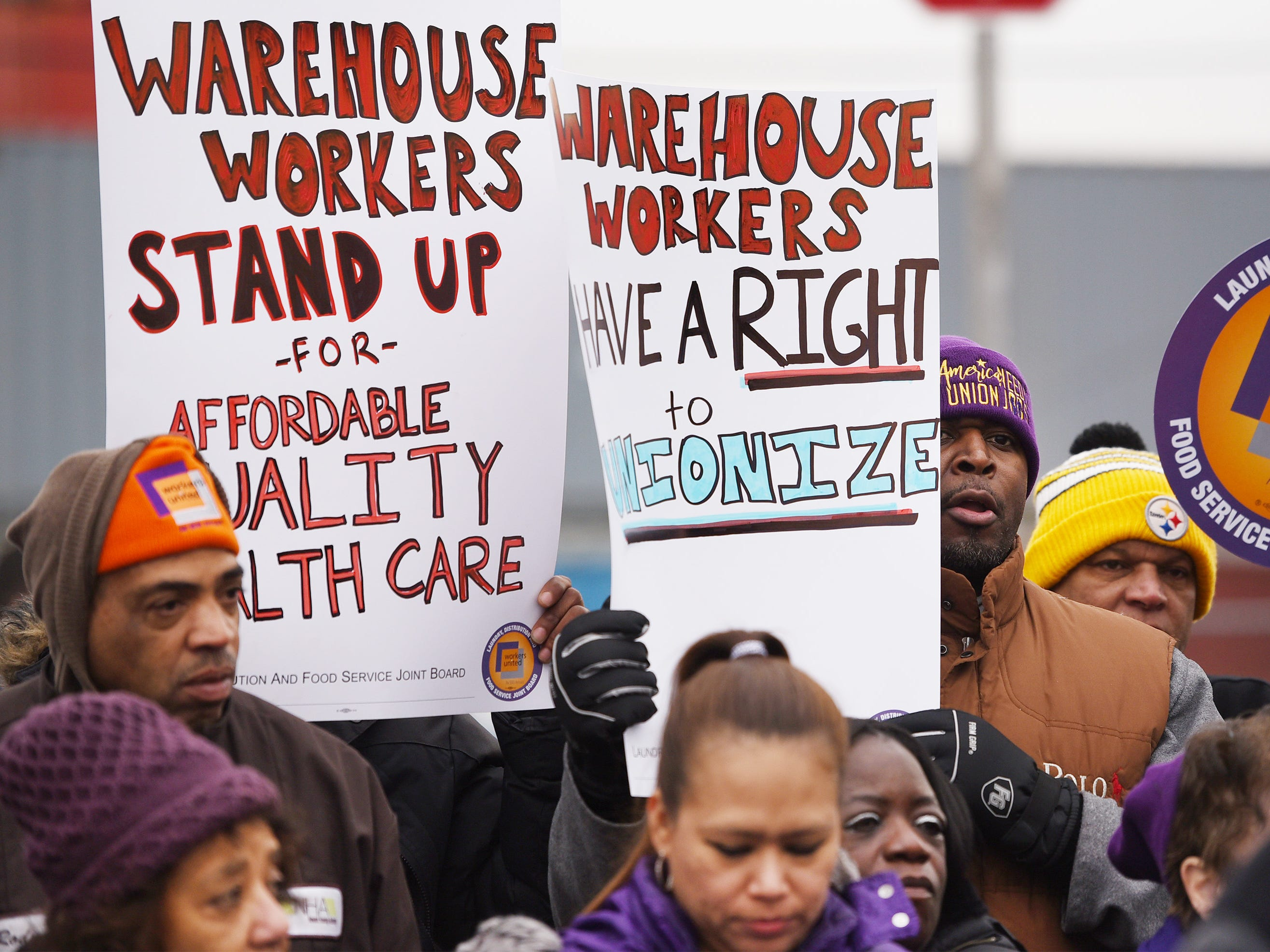 Workers hold up placards during a press conference at the Port of Newark to call for greater protections for warehouse workers, photographed at the corner of Corbin and Marsh streets in Newark on 12/12/18.
