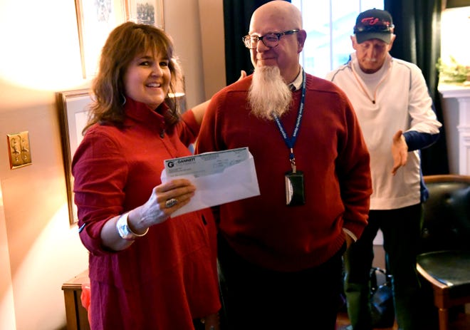 Grace Museum Executive Director Laura Moore receives a check from Abilene Reporter-News Editor Greg Jaklewicz for $5,000 for the museum Tuesday. The donation was in thanks for the support the newspaper received from its next-door neighbor during and in the aftermath of a fire Nov. 15.