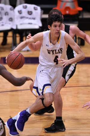 Wylie's Austin Brewer (4) drives past an Abilene High defender in a nondistrict game at Bulldog Gym on Tuesday, Dec. 11, 2018. The Eagles pulled out a 52-49 win.
