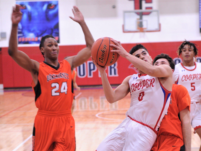Cooper's Josh Henry drives to the basket past a Burkburnett defender. Burkburnett won the game 89-76 on Tuesday, Dec. 11, 2018, at Cougar Gym.
