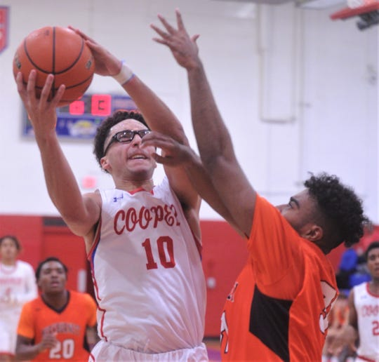 Cooper's Ben Thompson, left, drives to the basket while a Burkburnett player defends. Burkburnett won the game 89-76 on Tuesday, Dec. 11, 2018, at Cougar Gym.