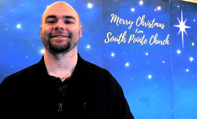 "Jamie Pope took a long, sometimes tough road, his position as teaching and vision pastor of South Pointe Church. Guests at a recent community Christmas celebration were invited to get their photo taken in front of this ""Merry Christmas"" sign."
