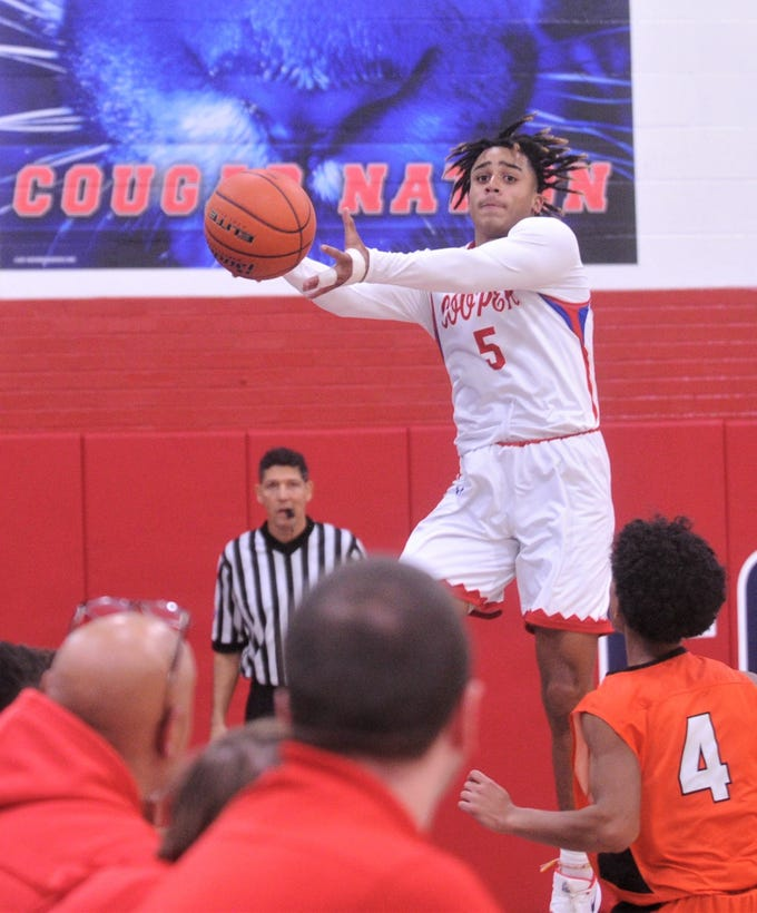 Cooper's Aeneas Favors (5) grabs the ball before it goes out of bounds in front of the Cougars' bench while Burkburnett's Jaevion Moreland (4) looks on. Burkburnett won the game 89-76 on Tuesday, Dec. 11, 2018, at Cougar Gym.