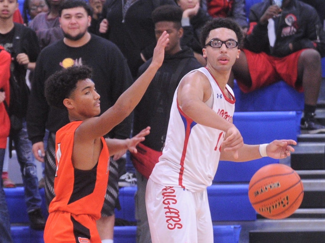 Cooper's Ben Thompson, right, passes the ball to a teammate while a Burkburnett player defends. Burkburnett won the game 89-76 on Tuesday, Dec. 11, 2018, at Cougar Gym.