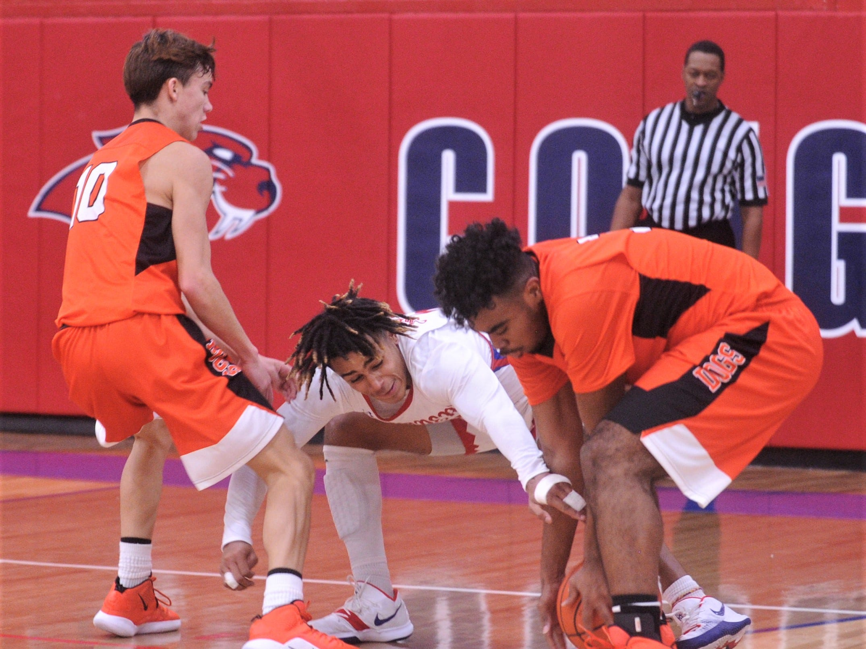 Cooper's Aeneas Favors, center, battles a Burkburnett player for a loose ball. Burkburnett won the game 89-76 on Tuesday, Dec. 11, 2018, at Cougar Gym.