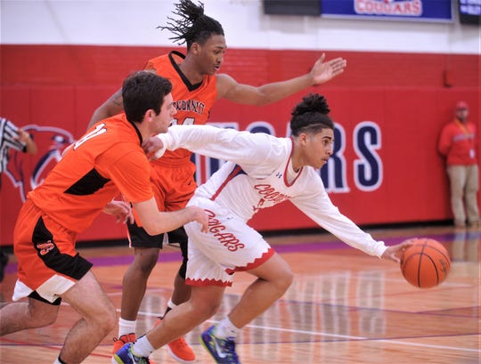 Cooper's Noah Garcia, right, brings the ball upcourt while Burkburnett's Gavin Morris, left, and Lucas Prayer give chase. Burkburnett won the game 89-76 on Tuesday, Dec. 11, 2018, at Cougar Gym.