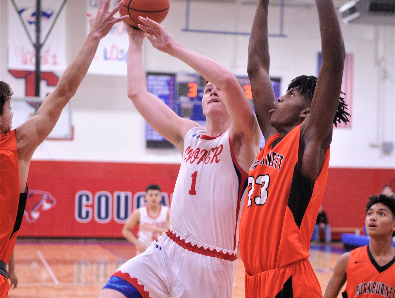 Cooper's Deven Bailey (1) drives to the basket as Burkburnett's Tre'Von Dean (23) defends. Burkburnett won the game 89-76 on Tuesday, Dec. 11, 2018, at Cougar Gym.