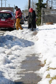 """Nicholas Rake and Gabrielle Wirth step over a pile of snow to to cross Haywood Road in West Asheville Dec. 11, 2018. """"They are difficult to navigate,"""" Wirth said of the ice and snow-covered sidewalks."""