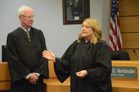 Judge James Norlander listens as the newst district court judge, Tracie Tomak, thanks family and supporters who attending her swearing in Wednesday, Dec. 12, 2018.