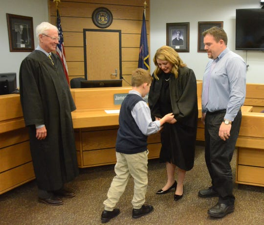 Judge Tracie Tomak is helped with her robe by son, Nicholas, as Judge James Norlander and her husband, Jon Galbreath, watch on Wednesday, Dec. 12, 2018.