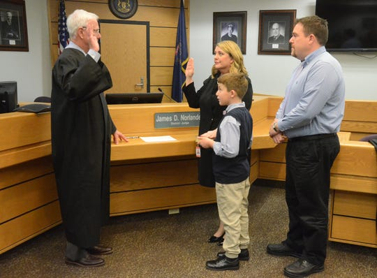 Judge James Norlander administers the oath to Tracie Tomak, who became the first female Calhoun County District Court judge. Husband Jon Galbreath and the couple's son, Nicholas, watch on Wednesday, Dec. 12, 2018.