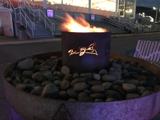 A fire outside of the Tioga Downs ractrack helps to keep Winterfest attendees warm on cold nights.