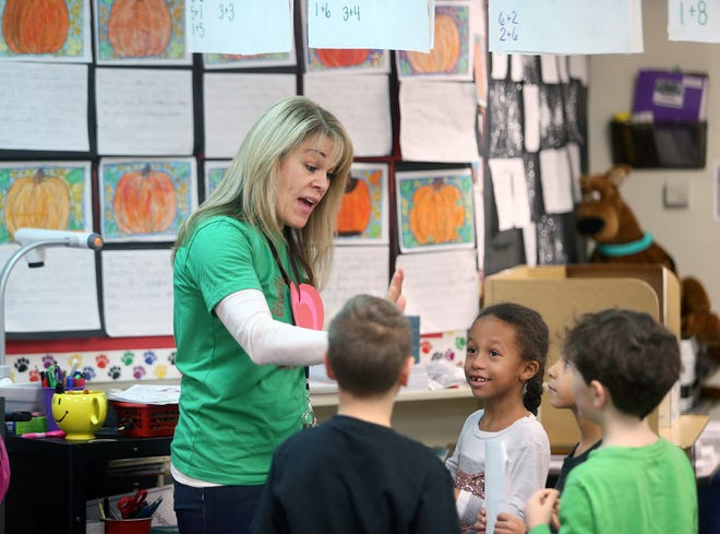 Janice LaFountaine, a first-grade teacher at Crownhill Elementary School in Bremerton, gives out student high-fives.