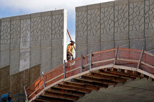 A worker walks past a gap where tall panels are being erected on a wildlife bridge under construction over Interstate 90 on Snoqualmie Pass. The stretch of highway crossing the Cascade Mountains cuts through old growth forest and wetlands, creating a dangerous border for wildlife everything from an elk down to a small salamander. The new crossing gives animals in these mountains a safer option for crossing the road: They'll be able to go above it.