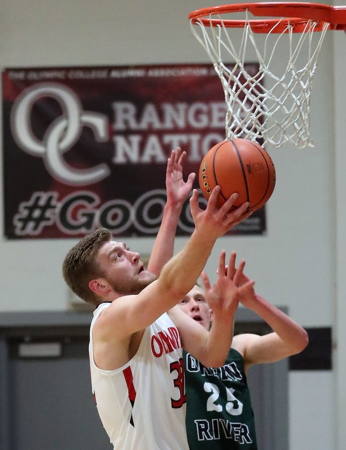 Olympic College's Calvin Dennis goes up for a shot over Green River's Alex Sommerfield at Olympic College in Bremerton on Tuesday, December 11, 2018.