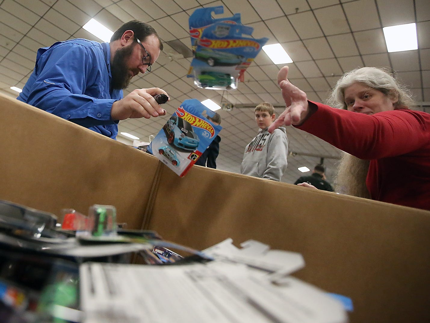 Volunteers Jared Kelly and Kathy Owen toss Hot Wheels cars into a box as they sort and mark donations for the upcoming Toys For Tots event in President's Hall at the Kitsap County Fairgrounds on Tuesday, December 11, 2018.