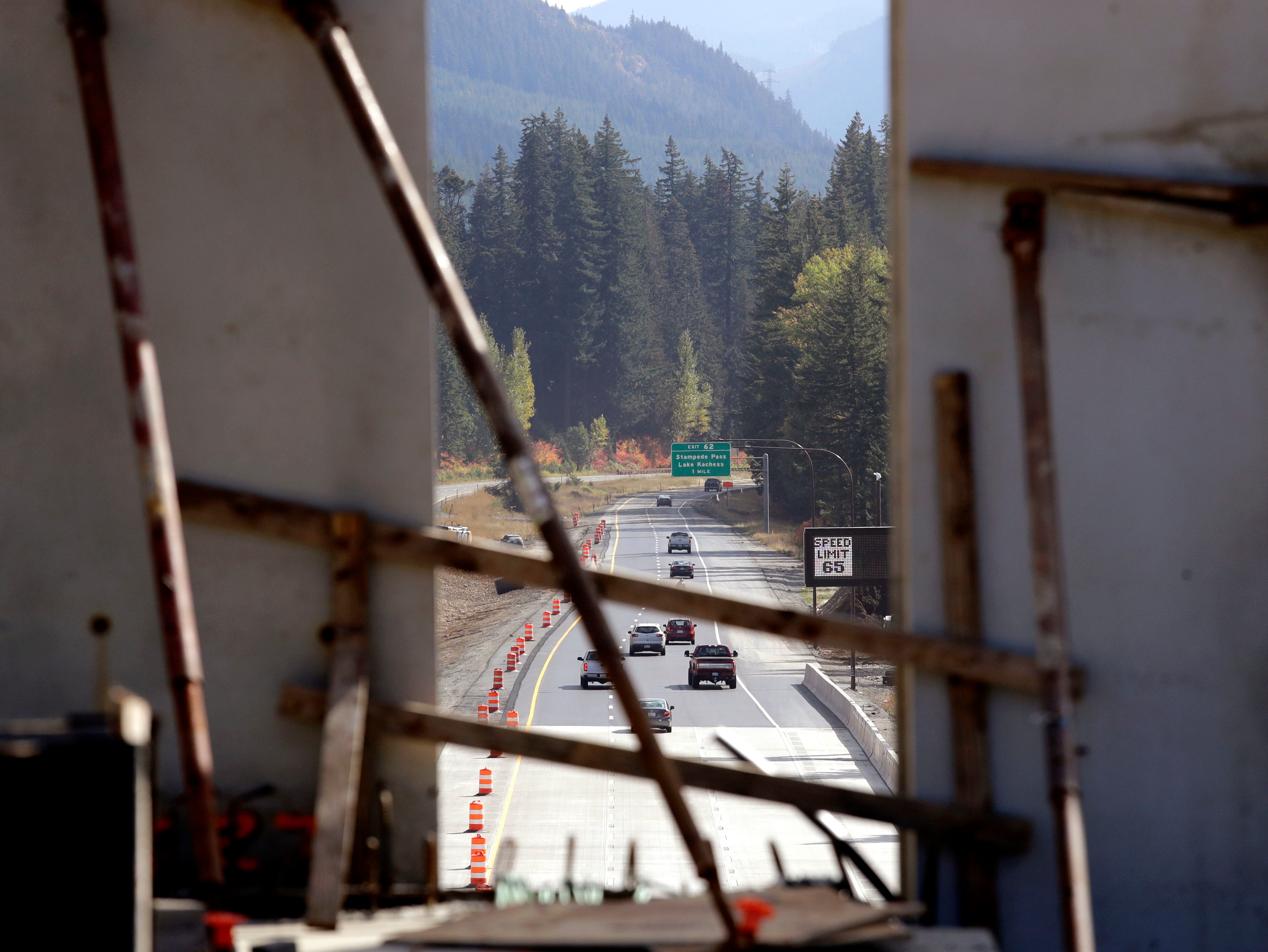Interstate 90 traffic passes beneath a wildlife bridge under construction is seen through a gap where tall panels are being erected on Snoqualmie Pass, Wash. The stretch of highway crossing the Cascade Mountains cuts through old growth forest and wetlands, creating a dangerous border for wildlife everything from an elk down to a small salamander. The new crossing gives animals in these mountains a safer option for crossing the road: They'll be able to go above it. (AP Photo/Elaine Thompson)