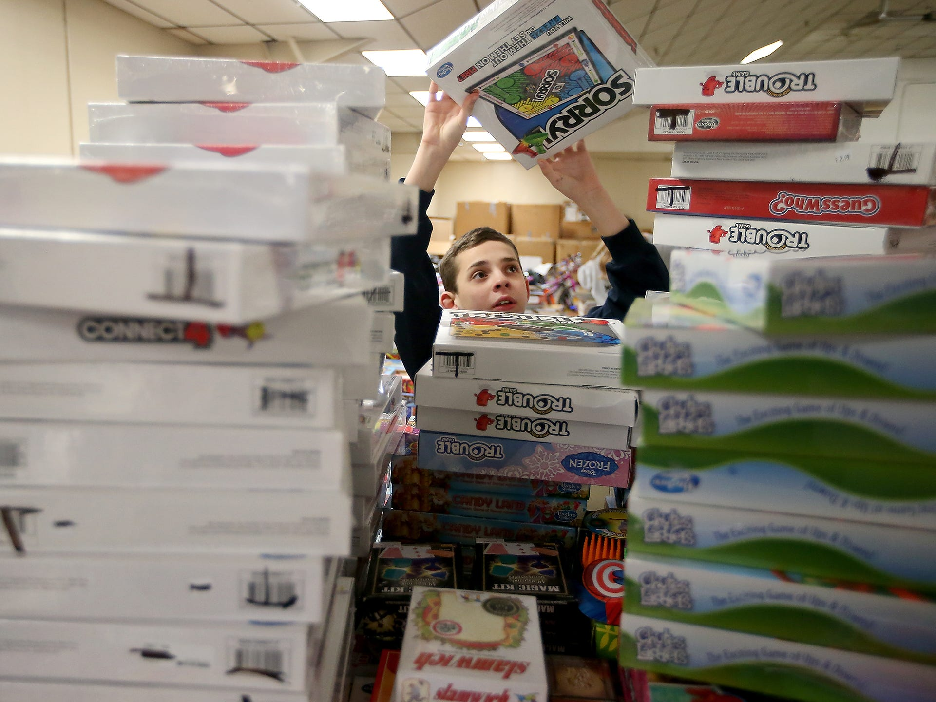 Volunteer Levi Bellon, 11, stacks board games as he helps set up for the upcoming Toys For Tots event in President's Hall at the Kitsap County Fairgrounds on Tuesday, December 11, 2018.