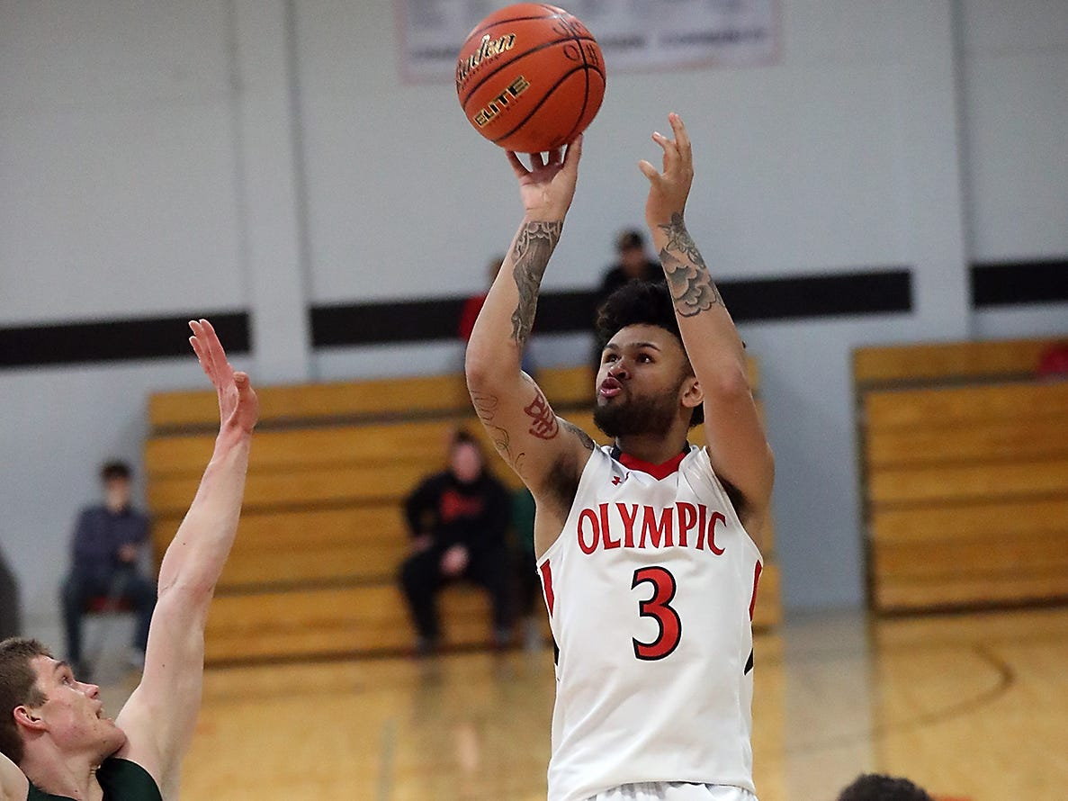 OC's Jaiden Mosely takes a shot over Green River's Mitch Wetmore at Olympic College in Bremerton on Tuesday, December 11, 2018.